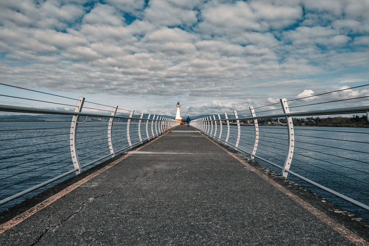 Rear view of man standing on pier by sea against sky
