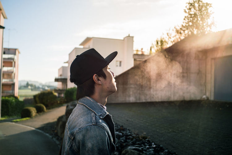 Side view of young man standing in city during sunset
