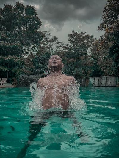 Man swimming in pool against trees