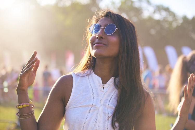 Thoughtful beautiful woman gesturing at carnival