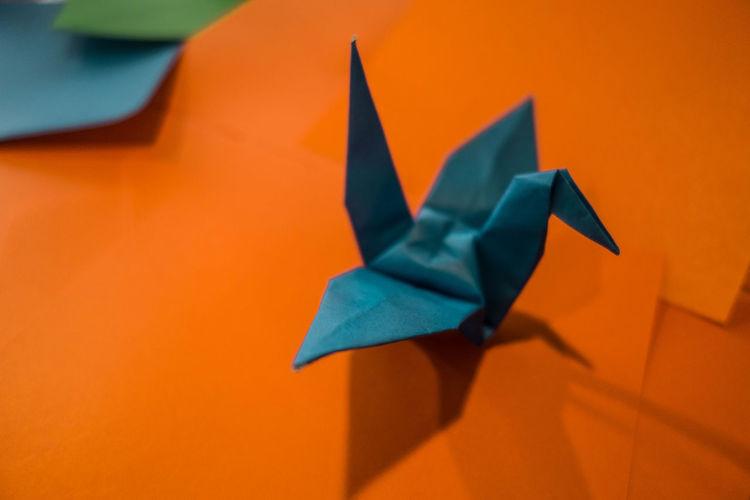 Close-Up Of Paper Bird Against Orange Background