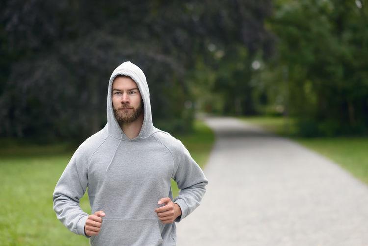 Handsome man jogging on footpath in park