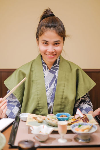 young Asian woman wearing Yukata with Japanese Dinner set and appetizer on wooden table in Traditional ryokan resort at Kawaguchiko lake, Yamanashi, Japan Smiling Portrait Food And Drink Front View Happiness Looking At Camera Indoors  One Person Food Table Emotion Child Sitting Lifestyles Holding Women Waist Up Leisure Activity Casual Clothing Meal Breakfast Japanese Food
