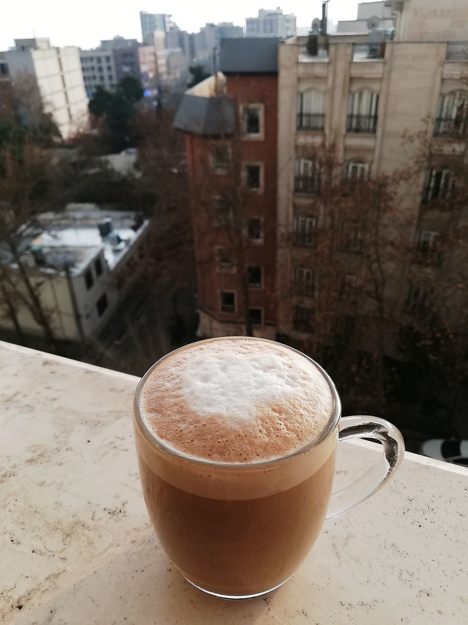 CLOSE-UP OF COFFEE ON TABLE AGAINST BUILDINGS