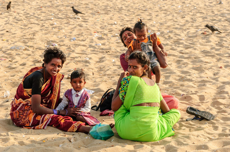 Mothers and children sitting on the beach, Chennai, India. Chennai India Beach Bonding Boys Child Childhood Family Fun Girls Happiness Leisure Activity Love Mothers And Children Outdoors Real People Sand Sitting Smiling Son Sunlight Togetherness Vacations