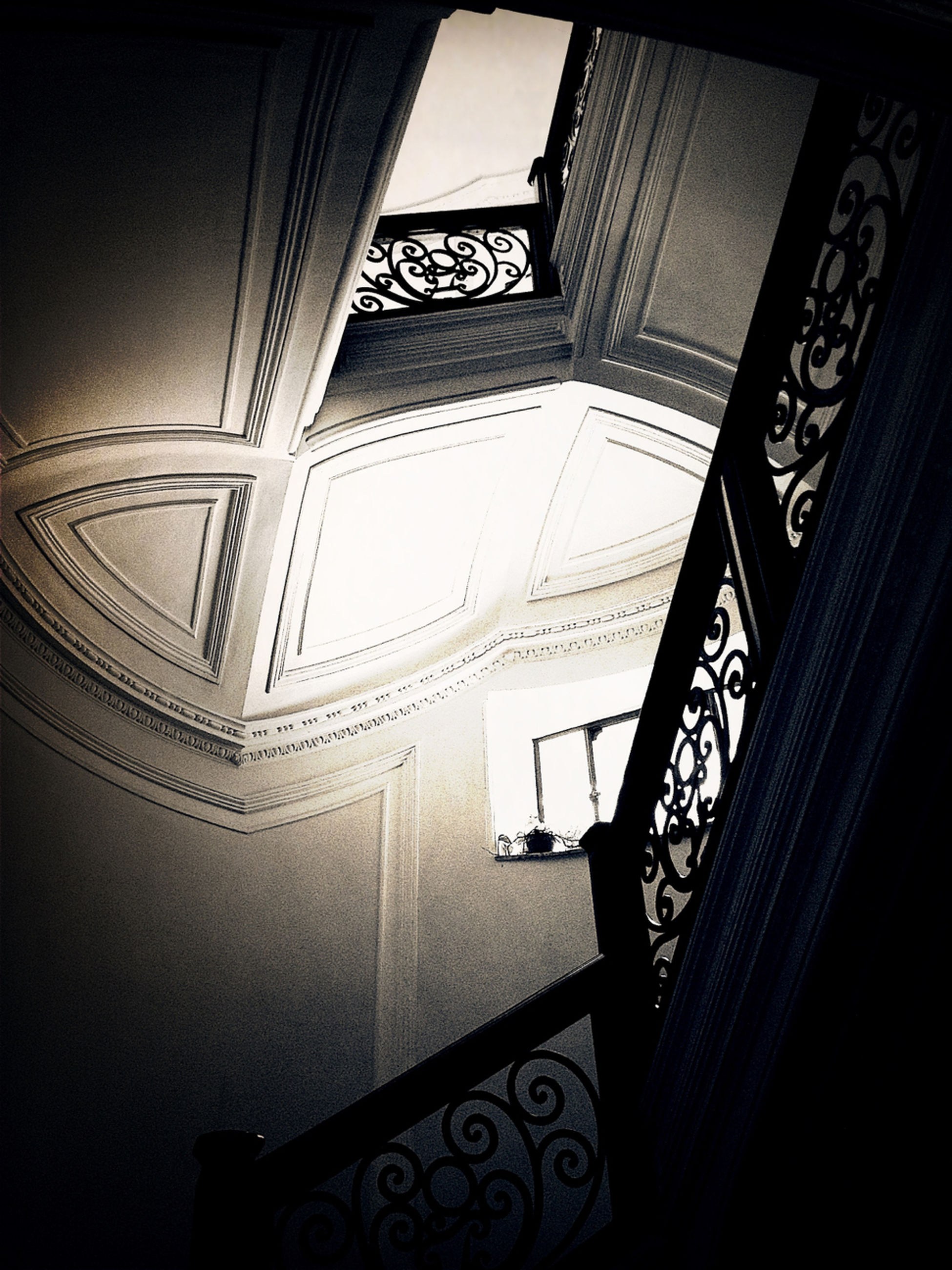 indoors, architecture, built structure, low angle view, ceiling, design, pattern, railing, staircase, steps, steps and staircases, window, building, architectural feature, directly below, sunlight, building exterior, no people, skylight, shadow