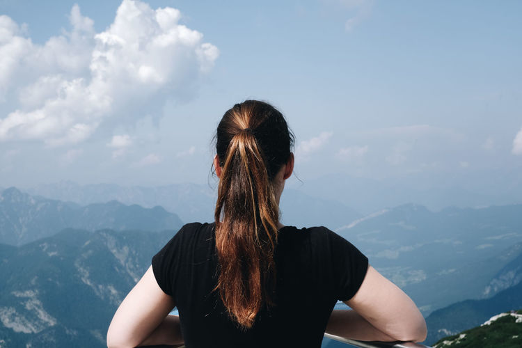 Rear view of woman standing against mountains and sky