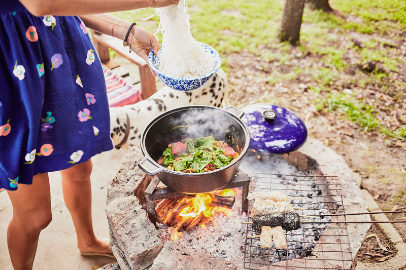 Low Section Of Woman Preparing Food At Barbecue Grill
