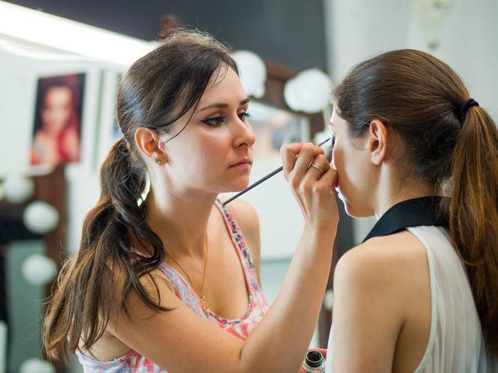 Artist Applying Make-Up On Woman In Beauty Spa