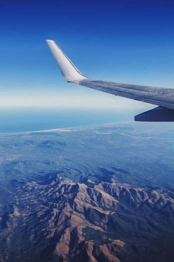 Aerial view of airplane wing over sea