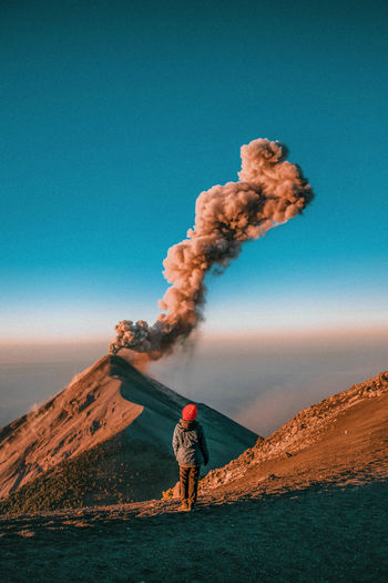 Morning eruptions Guatemala Orange Smoke Adventure Beauty In Nature Blue Day Environment Geology Hike Hiker Land Landscape Mountain Nature One Person Outdoors Power In Nature Real People Sky Standing Sun Sunrise Volcanic Crater Volcano The Traveler - 2018 EyeEm Awards The Great Outdoors - 2018 EyeEm Awards Be Brave