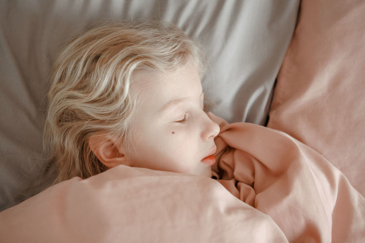 Closeup of cute caucasian blonde girl child sleeping dreaming in bed at home. sleep tired kid