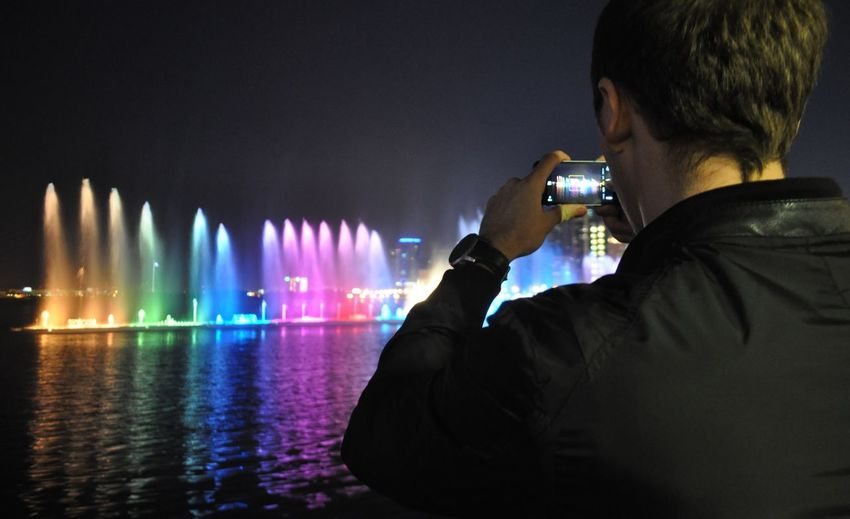 Rear View Of Man Photographing Illuminated Fountain At Al Majaz Park Sharjah