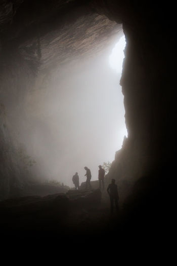 Silhouette Friends Standing In Cave During Foggy Weather