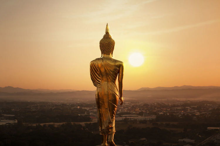 Golden Buddha Statue in the Morning,Nan province,Thailand Architecture Built Structure Sky Sunset Religion Belief Building Exterior Spirituality City Building Human Representation Statue Sculpture No People Place Of Worship Nature Art And Craft Cityscape Sun Outdoors Buddha