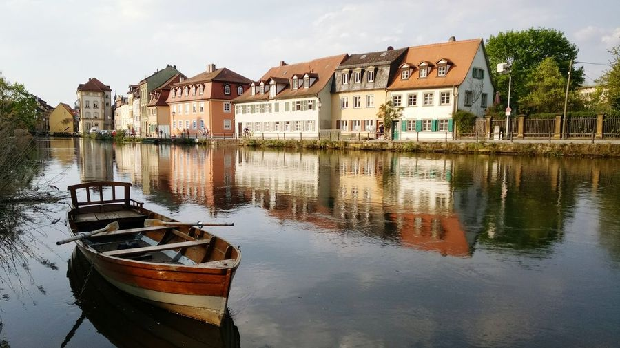 Boats Moored In Lake By Houses Against Buildings