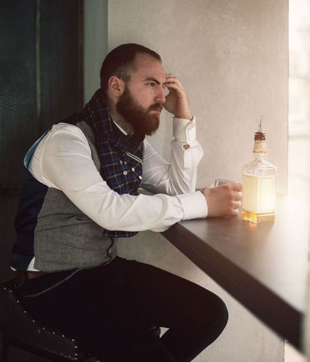Side View Of Thoughtful Bearded Man With Drink Sitting At Home