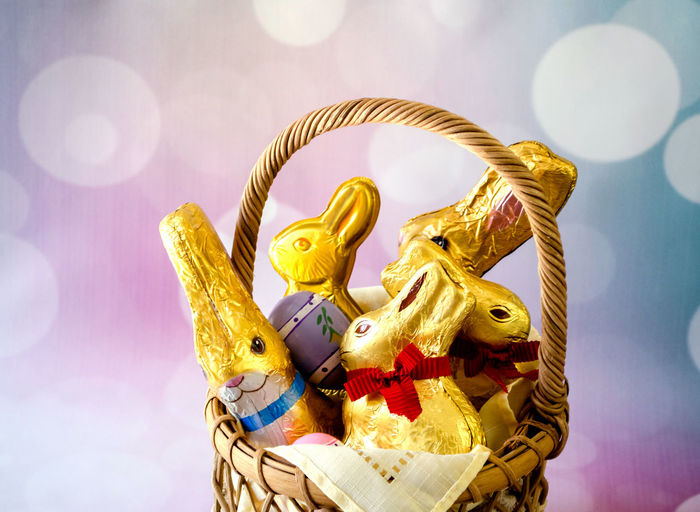 Close-up of easter bunnies with eggs and wicker basket against abstract backgrounds