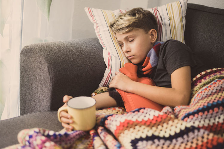 Sick boy holding milk cup while lying don on sofa at home