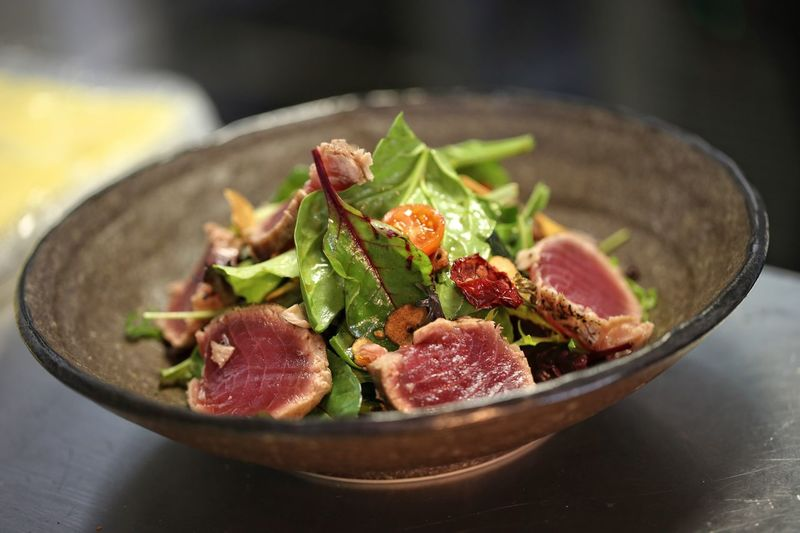 Close-Up Of Tuna Slices And Leaves In Bowl On Table