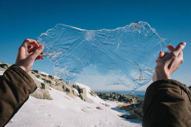 Cropped image of person holding ice on snow field against clear sky
