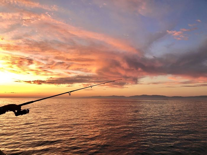 Silhouette fishing rod on sea against sky during sunset