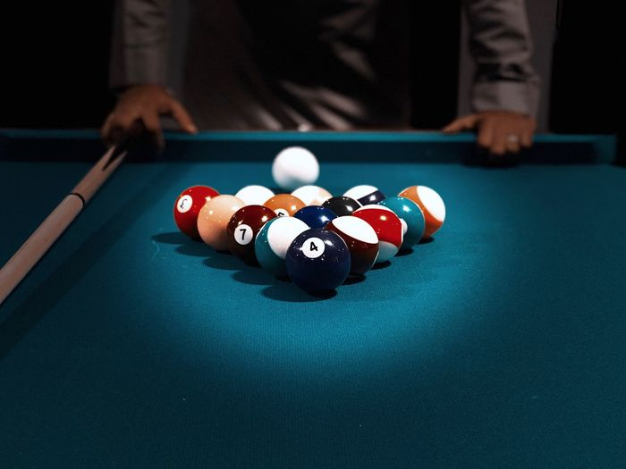 Close-up of pool table with man in background