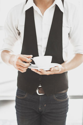 Midsection Of Man Holding Coffee Cup Against Door