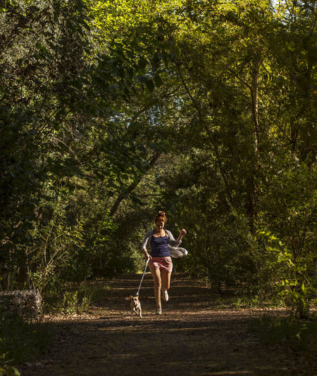 Woman with dog running amidst trees at forest