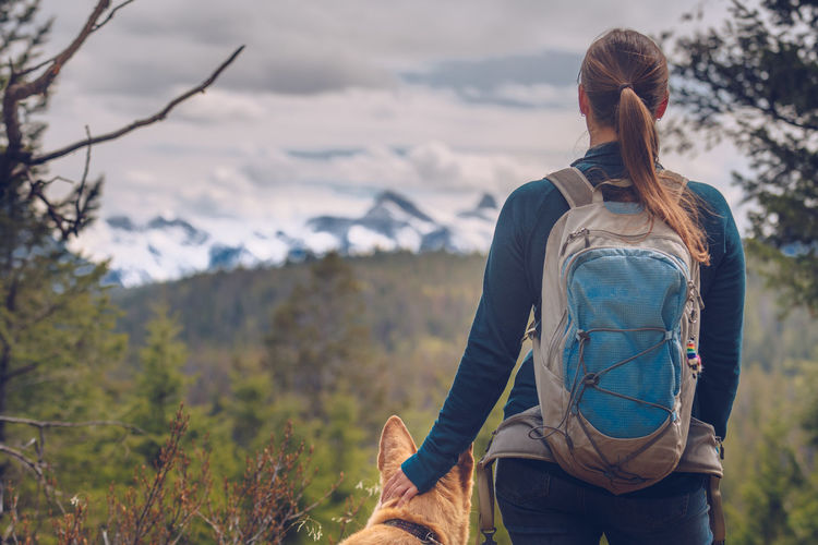 Rear view of woman with dog against snowcapped mountain