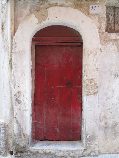 red wooden door Architecture Door Entrance Built Structure Building Exterior Building Red Closed Day Arch No People Old Outdoors Wall - Building Feature Wall House Weathered