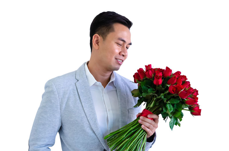 Man holding red flower against white background