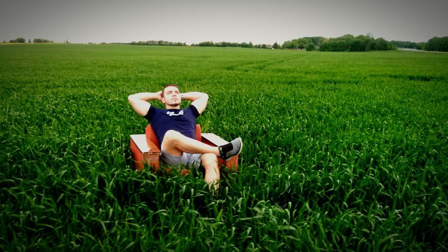 Man Sitting In Sofa In Field