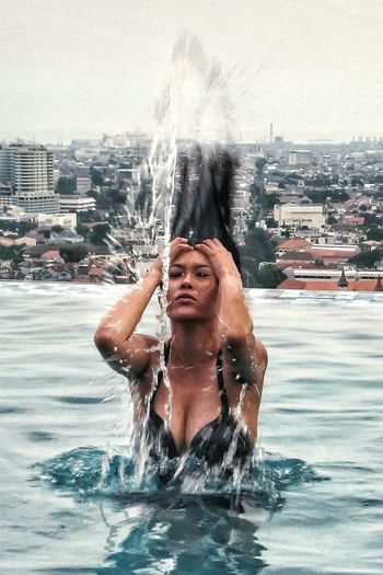 Sensuous Woman Tossing Hair In Infinity Pool Against Cityscape