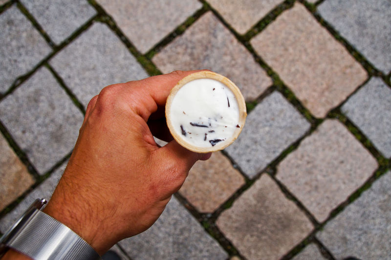 Cropped image of hand holding ice cream cone on paved footpath