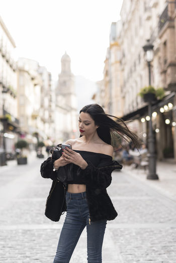 Young woman using mobile phone while standing on street in city