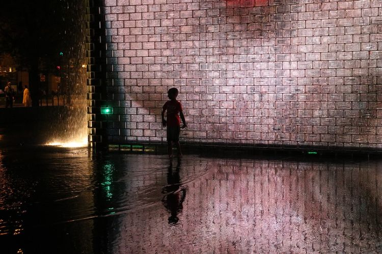 Glowing Fountain Light Architecture Brick Built Structure City Illuminated Light And Shadow Night One Person Reflection Silhouette Standing Street Street Photography Walking Wall Wall - Building Feature Water