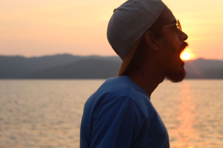 Side view of young man standing by sea against sky during sunset