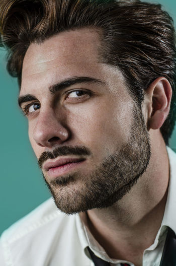 One Person Portrait Headshot Young Adult Close-up Beard Adult Beautiful People Handsome Facial Hair Young Men Stubble Looking Serious Lifestyles Human Face Hairstyle Looking At Camera Hipster Hipster Style White Shirt Blue Background Tourquise