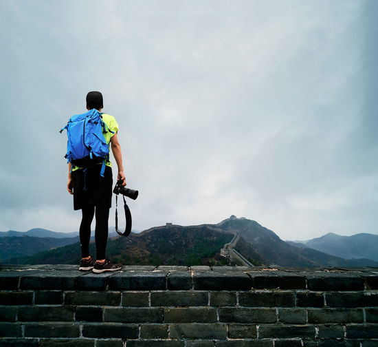 Rear view of backpacker standing on retaining wall against cloudy sky