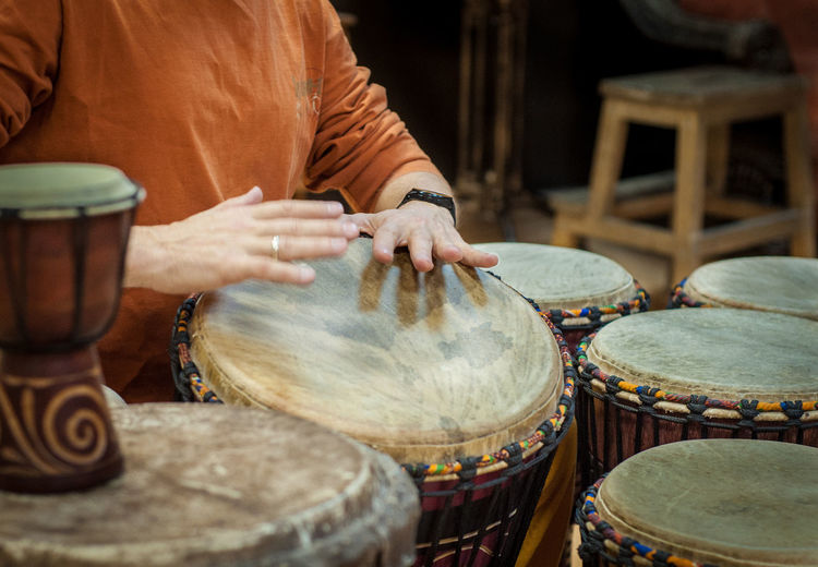 Midsection of woman playing drum