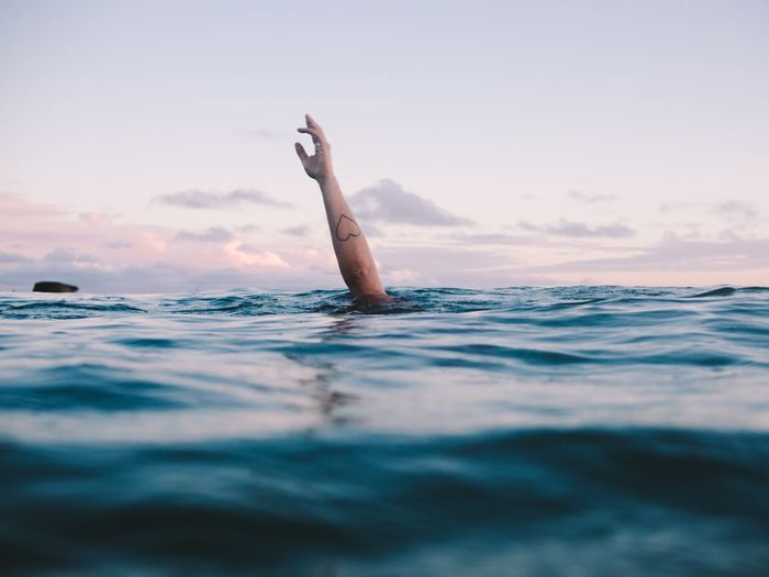 Cropped Image Of Woman Hand Drowning In Sea Against Sky