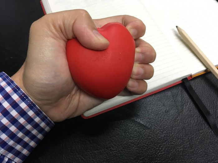 Stressed Stress Ball Human Body Part Human Hand One Person Hand Holding Real People Red Indoors  Body Part Finger Human Finger Close-up Lifestyles Unrecognizable Person Book Personal Perspective Publication Leisure Activity Table