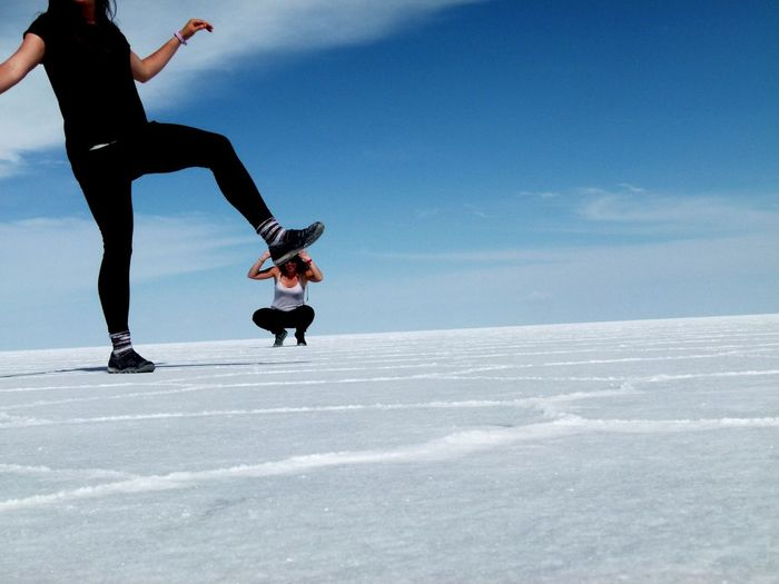Optical illusion of woman pressing friend with foot at salar de uyuni