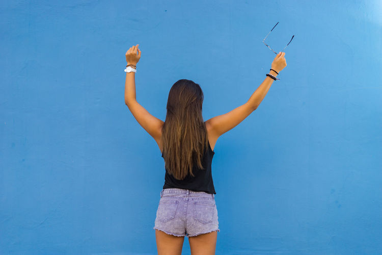 Rear view of teenage girl with arms raised standing against wall