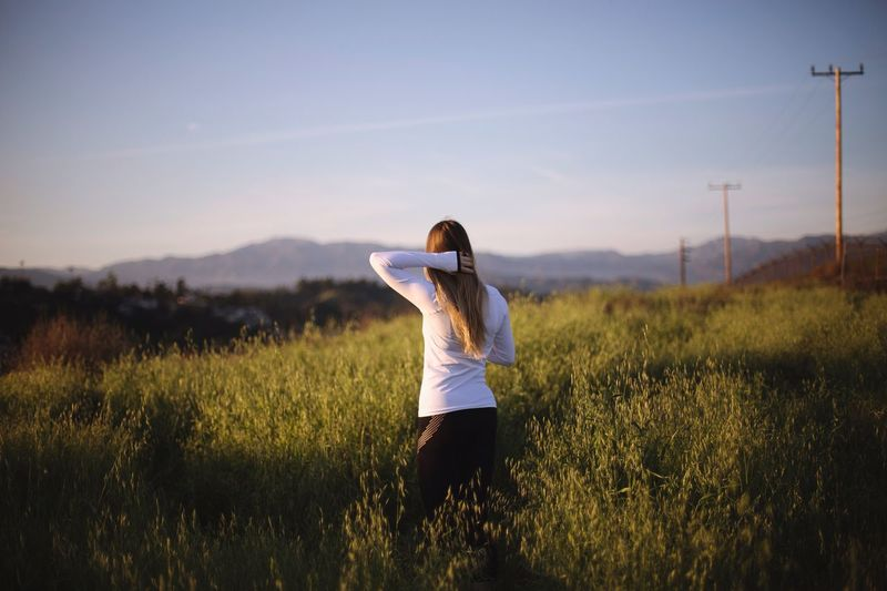 Rear view of woman standing on grassy field against sky during sunset