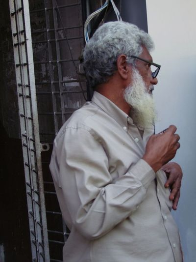 Portait of a Myanmar Man Deep in Thought! Beard China Town City City Lifestyle Composition Deep In Thought Full Frame Glasses Grey Hair Man Myanmar One Man Only One Person Outdoor Photography Real People Side View Travel Destination Waist Up White Beard Yangon