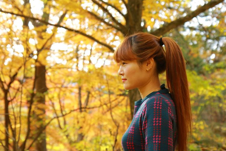 Side view of young woman standing in park during autumn
