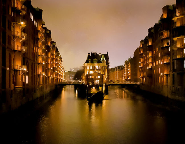Arch bridge over canal amidst buildings in city at night