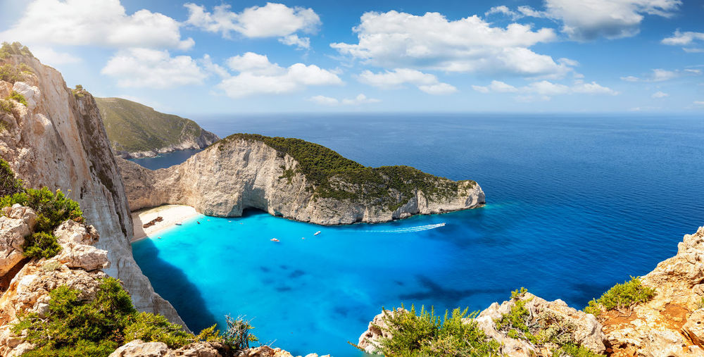 Panoramic view to the famous shipwreck beach, Navagio, on the island of Zakynthos, Greece, on a cloudy summer day Water Scenics - Nature Sky Sea Tranquil Scene Beauty In Nature Cloud - Sky Tranquility Blue Idyllic Day High Angle View Rock Horizon Over Water Turquoise Colored Outdoors Nature Zakynthos Greece Mediterranean  Island Ionian Sea Ionian Islands Shipwreck Shipwreck Beach Navagio Tourist Attraction  Travel Destinations Summer Clouds Turquoise Water Panorama No People